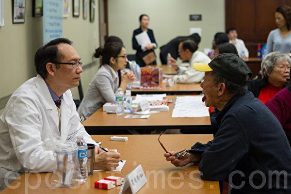 莫偉明中醫師(左一)為民眾檢查舌苔。(李歐/大紀元)