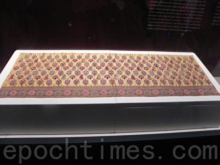 """在""""绚丽多姿—院藏南亚服饰特展""""中展出的《黄地女郎、孔雀与花束纹刺绣裙》,是印度20世纪早期的作品。(蔡上海/大纪元)"""
