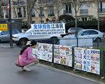 图为巴黎铁塔下的真相点上,大陆游客观看法轮功真相展版。(张宇芳/大纪元)