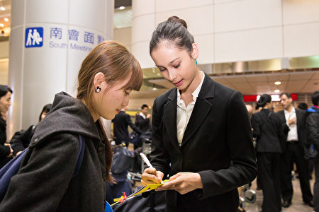 2016年3月14日晚間10點半左右,來自美國紐約的神韻世界藝術團抵達台灣,舞蹈演員為熱情粉絲簽名。(陳柏州/大紀元)