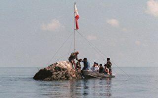 1997年5月17日,菲律宾海军人员和三名国会议员把菲律宾国旗插到黄岩岛上。 (JESS YUSON/AFP)