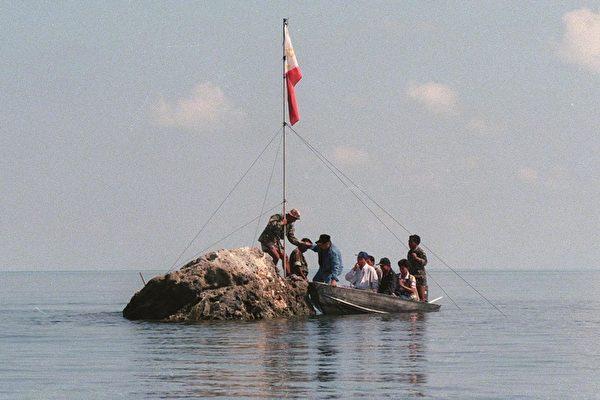 1997年5月17日,菲律宾海军人员和三名国会议员把菲律宾国旗插到黄岩岛上。<br /> (JESS YUSON/AFP)