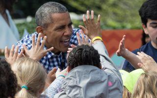 3月28日,美国总统奥巴马在一年一度的白宫复活节滚彩蛋活动中与儿童们拍手互动。   (NICHOLAS KAMM/AFP/Getty Images)