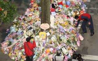 """不少民众到""""小灯泡""""离世的环山路现场献花祝祷、点灯。民众所摆放的鲜花、蜡烛、卡片或各式玩具,已在环山路上延绵100米以上。(中央社)"""
