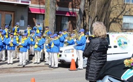 圖8:多倫多市民Christina在起點處觀看天國樂團排練時,一直拿著手機在錄像。(明慧網)