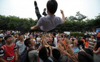 近幾十年來,為擺脫中國填鴨式教育及升學壓力的理由,越來越多的中國父母將仍是青春期的孩子送到美國就讀私校高中。圖為2014年重慶一所高中學生在高考完後高興地將老師抛向空中。(AFP)
