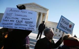 今天(3月29日),美國最高法院八名法官審理有關公務員未加入工會但被要求繳納相當於會費費用之爭議,裁決結果是4比4,工會對此結果表示歡迎。圖為2016年1月支持工會及教師的群眾在最高法院前手持標語。 (Photo by Mark Wilson/Getty Images)