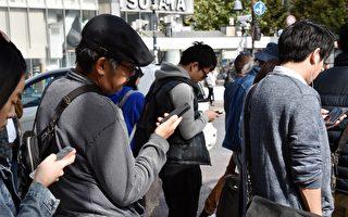 這張照片攝於2014年11月3日,顯示了東京街頭上使用智能手機穿越馬路的行人佔大多數,這些人緊盯著智能手機過馬路。(YOSHIKAZU TSUNO/AFP/Getty Images)