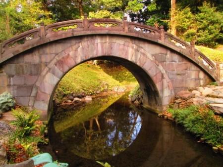 圓月橋的橋拱在水中倒影如一輪明月。(容乃加/大紀元)