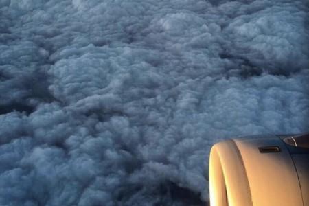"""图片显示在飞机上航拍穿越红色预警重污染中的北京雾霾层。该图片此前曾引发网民热议,有评论形容:""""云层之下,恍如地狱""""。(网络图片)"""