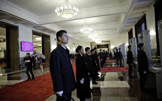 """2016年4月11日,中纪委关机报头版头条刊发题为""""力度不减 节奏不变""""的从严治党系列文章,释放强烈政治信号。图为,2016年3月14日,站在人民大会堂内准备进行安检的保安人员。(Lintao Zhang/Getty Images)"""