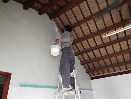65歲,手腳俐落的吳老闆,不管多高的牆他有辦法粉刷。(廖素貞/大紀元)