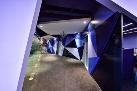 鑽石切割法的菱菱角角帶出了空間的現代感,但蔡竺欣刻意在走廊上,保留了兩盞水晶燈,預告著《大紀元》在不久的將來,將回歸到古典,那是未來的輝煌。(克俐凱文建築空間設計提供)