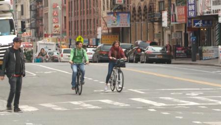 在华埠骑车的民众。 (李凯文/大纪元)