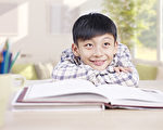 10 year-old asian schoolboy resting his head on arms and daydreaming.