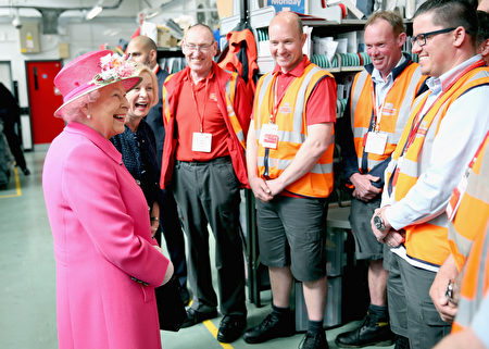 WINDSOR, ENGLAND - APRIL 20: Queen Elizabeth II shares a joke with postmen about their shorts as she visits the Queen Elizabeth II delivery office in Windsor with Prince Philip, Duke of Edinburgh on April 20, 2016 in Windsor, England. The visit marks the 500th Anniversary of the Royal Mail delivery service. The Queen and Duke of Edinburgh are carrying out engagements in Windsor ahead of the Queen's 90th Birthday tommorow. (Photo by Chris Jackson - WPA Pool/Getty Images)