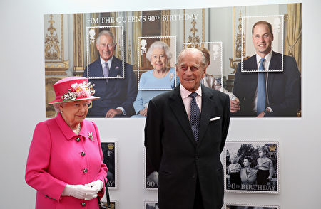 Britain's Queen Elizabeth II (L) and Britain's Prince Philip, Duke of Edinburgh pass a giant photograph taken to be used as part of a series of 10 Royal Mail postage stamps, to mark the monarch's 90th birthday, during her tour of the Royal Mail Windsor postal delivery office in Windsor, west of London, on April 20, 2016, to mark the 500th anniversary of the Postal Service. Queen Elizabeth II is set to celebrate her 90th birthday on April 21, with a family gathering and a cake baked by a reality television star, as a new poll finds Britain's longest serving monarch is as popular as ever. The queen has reigned for more than 63 years and shows no sign of retiring, even if she has in recent years passed on some of her duties to the younger royals. / AFP / POOL / Chris Jackson (Photo credit should read CHRIS JACKSON/AFP/Getty Images)