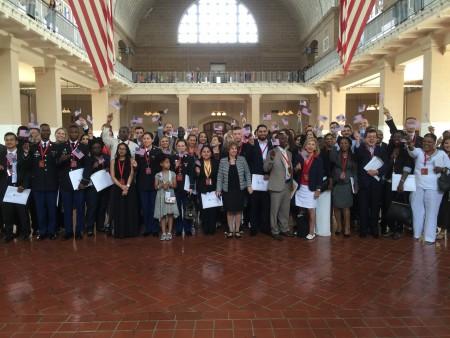 61个新公民在艾利斯岛移民博物馆大厅中合影。