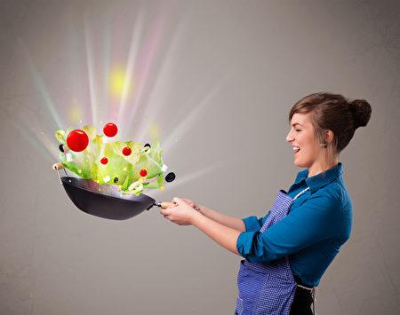 年轻漂亮的女人烹调新鲜蔬菜与抽象灯(fotolia)