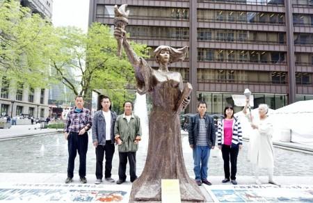 雕塑家陳維明(左三)和同行的義工一起與豎立在戴利廣場的民主女神像合照。(溫文清/大紀元)
