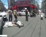 台湾嘉义市85岁吴姓老翁30日中午过马路时,疑似天气炎热、一时头晕而发生车祸,由热心的路人为他打伞遮阳,所幸送医后并无大碍。(民众提供)