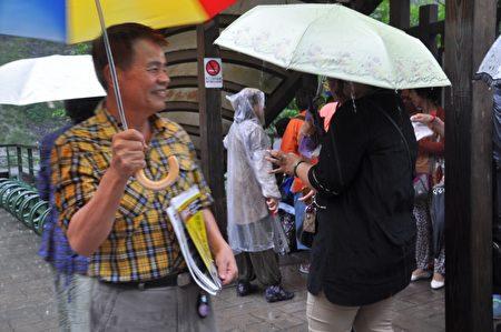 法轮功学员童石海(黄格上衣),夫妻俩不论刮风下雨,都开着车到太鲁阁长春祠发资料给陆客及劝三退。(詹亦菱/大纪元)