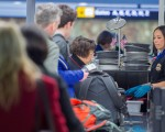 美国交通安全管理局(TSA)日前正在测试新的安检措施,要求搭机乘客从包中取出任何大于手机的电子产品及食品,并对这些物品进行分别扫描。( PAUL J. RICHARDS/AFP/Getty Images)
