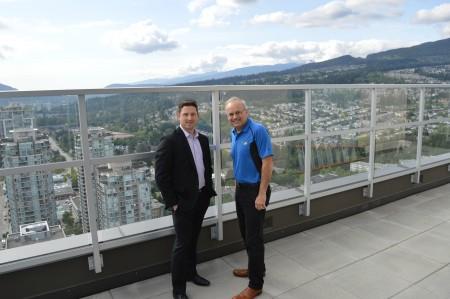 高贵林市长斯沃特(右)与开发商Cressey副总裁托柯特在MThree顶楼阳台合影,背景是北岸连绵山峦。(张可欣/大纪元)