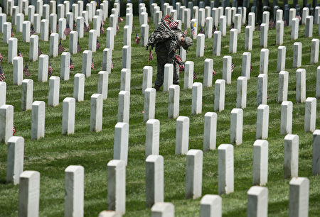 WASHINGTON, DC - MAY 26: A member of the 3rd U.S. Infantry Regiment, 'The Old Guard,' places a flag at a grave site during the 'Flags-In' ceremony May 26, 2016 at Arlington National Cemetery in Arlington, Virginia. A small American flag was placed one foot in front of more than 220,000 graves in the cemetery to mark Memorial Day. (Photo by Mark Wilson/Getty Images)