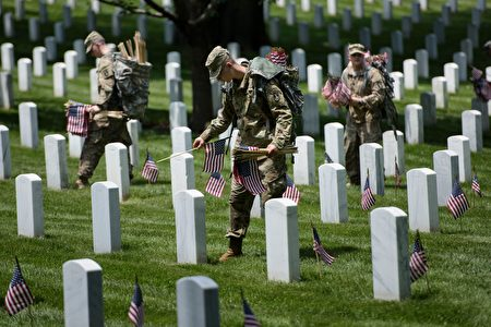 Members of the US Army place American flags at graves at Arlington National Cemetery May 26, 2016 in Arlington, Virginia in preparation for Memorial Day. / AFP / Brendan Smialowski (Photo credit should read BRENDAN SMIALOWSKI/AFP/Getty Images)