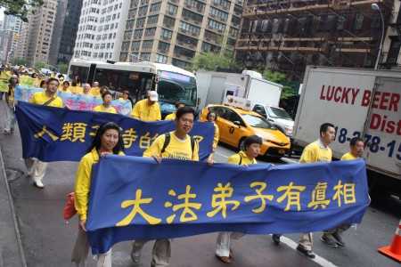 """2016年5月13日,纽约上万人游行庆祝第17届法轮大法日。有学员举着横幅:""""人类等待的来了,大法弟子有真相""""。(马有志/大纪元)"""