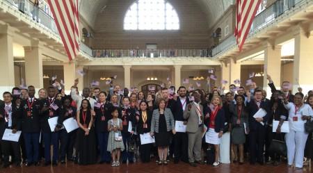61名新公民在艾利斯岛移民博物馆大厅中合影。