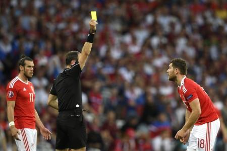 威爾斯的沃克斯(Sam Vokes)犯規吃到一張黃牌。 (MARTIN BUREAU/AFP)