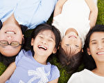 幸福的家庭躺在草地上一起(fotolia)