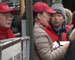 """去年,13位原告向美国纽约东区联邦地区法院控告CACWA及其两名共同主席朱立创(左)、李华红(左二)。图为朱立创和李华红在法拉盛游行结束后以""""餐票""""换""""红马甲""""的现场。(大纪元)"""