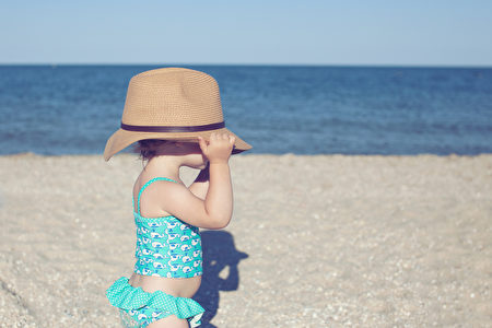 Cute toddler girl in big hat on the beach