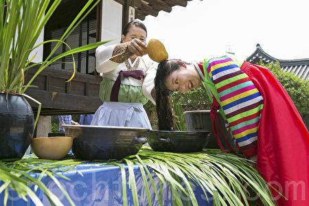 6月9日,韓國首爾南山韓屋村舉行端午節慶典千名中國遊客體驗韓國傳統文化與習俗。圖為用菖蒲水洗頭。(全景林/大紀元)