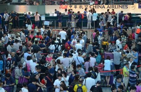 华航空服罢工虽落幕,但25日仍取消55班,逾1万名旅客受影响,地勤人力吃紧,旅客排长龙,绵延近数百米,充满无奈与煎熬的等待。(中央社)