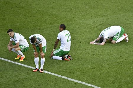 Dejected Northern Ireland players rest on the pitch after loosing 0-1 in a own goal during the Euro 2016 round of sixteen football match Wales vs Northern Ireland, on June 25, 2016 at the Parc des Princes stadium in Paris. / AFP / PHILIPPE LOPEZ (Photo credit should read PHILIPPE LOPEZ/AFP/Getty Images)