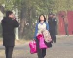 2013年11月6日,梁波手拿衣服,昂首走出北京女子监狱的大门。(大纪元)