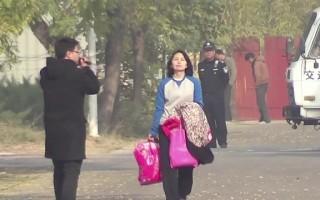 2013年11月6日,梁波手拿衣服,昂首走出北京女子監獄的大門。(大紀元)