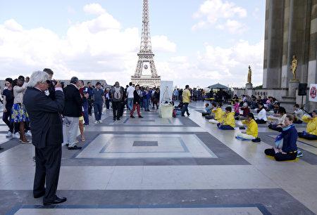二零一六年六月二十六日下午,法輪功學員在巴黎艾菲爾鐵塔下的人權廣場上傳播真相。圖為法輪功學員祥和的功法場面和真相展板都吸引了中西遊客的目光。(明慧網)