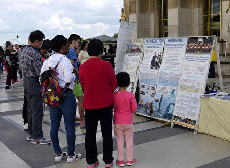 圖1-3:二零一六年六月二十六日下午,法輪功學員在巴黎艾菲爾鐵塔下的人權廣場上傳播真相。圖為法輪功學員祥和的功法場面和真相展板都吸引了中西遊客的目光。(明慧網)