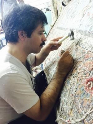 高貴的地毯之所以可以當傳家寶,是因為即使破損 也可經由修補還原一塊如新的地毯,圖為修補師傅細心的為地毯修補 。(Arsham 提供)