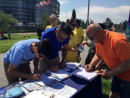 斯特拉斯堡欧洲议会大楼外,民众签名支持法轮功反迫害。(明慧网)