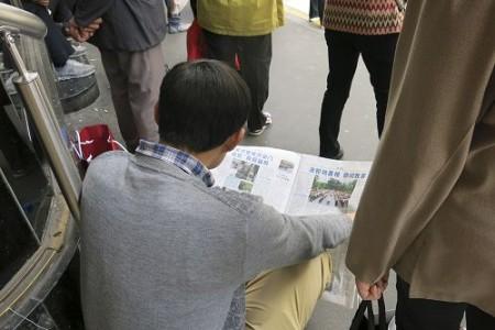 一名大陆游客坐在拉法耶特商场门前的台阶上认真阅读法轮功真相资料。(明慧网)