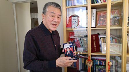 程國強教授手捧當年獲頒的文學藝術獎章。(邱晨/大紀元)