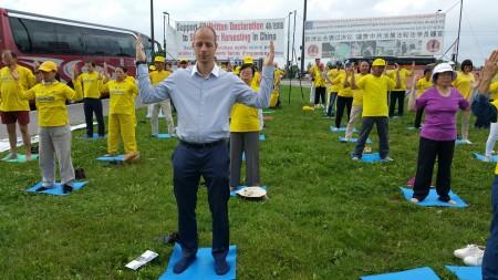 捷克欧洲议员的助手Lukas Bachta向法轮功学员学炼法轮功。(黎平/大纪元)