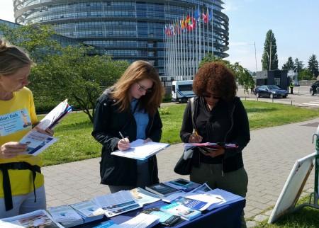 斯特拉斯堡欧洲议会大楼外,民众签名支持法轮功反迫害。(黎平/大纪元)