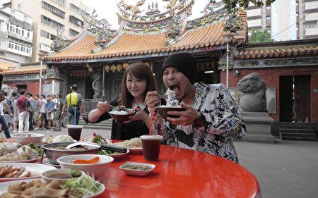 观传局长简余晏(左)与歌手黄明志大啖台北古早味美食。(台北市观传局提供)